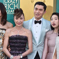 "Cast of ""Crazy Rich Asians"" in multicolored dresses and suit in front of gold and green background"
