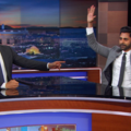 Trevor Noah, Hasan Minhaj. Two brown men sit in gray suits sit at large black-topped desk. One man points at the other, whose arms are above his head
