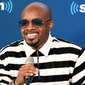 Jermaine Dupri in black sunglasses and black and white shirt holding black microphone in front of blue wall