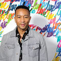 John Legend in grey jacket and black patterned shirt in front of white wall with multicolored paints