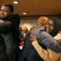 Odell Edwards in black suit hugs George Lewis in grey suit next to Charmaine Edwards in brown suit hugging Reggie Edwards in grey suit in front of courtroom audience in multicolored clothing and brown benches and wall