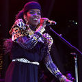 Lauryn Hill sings behind black microphone and stand while wearing black hat and black brown leopard-print hat in front of black wall and pink screen