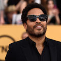 Lenny Kravitz in black suit and sunglasses in front of gold walls