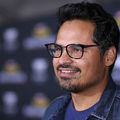 Michael Peña smiles in black glasses and  navy shirt in front of dark grey background with white logos