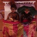 Stop-motion animation of Black couple in bed with white frame pink and yellow and blue comforter on brown wood floor
