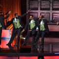 The Temptations and Dennis Edwards in black and green tuxedos behind black and grey microphones and stands in front of band on black stage with red and brown light