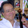Yo-Yo Ma. Man of Chinese descent smiles while wearing a white button-down shirt and playing a brown cello