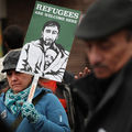 """Person in winter clothing holds green and white sign that reads, """"Refugees are welcome here."""""""