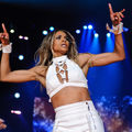 Ciara. Black woman in white outfit performs on stage with blue lights
