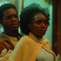 Stephan James and KiKi Layne. Black man in brown jacket and shirt holds Black woman in yellow sweater and light blue dress in front of brown wall and blue store lights