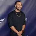 Jesse Williams. Black man with blue eyes in black shirt and gold necklace smiles in front of purple wall