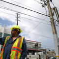 Latinx man in navy shirt and yellow construction hat and yellow and orange vest stands in front of brown and grey and green building and brown electrical poles with black power lines
