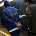 Incarcerated man in blue hat and pants and jacket with yellow letters in grey handcuffs held by corrections officer in green uniform and hat in front of black lockers and cells and grey floor with yellow stripe