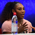 Serena Williams in pink shirt in front of blue screen and behind blue water bottle