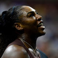 Serena Williams with black and blonde hair in brown and black athletic attire in front of blurry audience