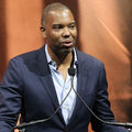Ta-Nehisi Coates in navy blazer and light blue dress shirt behind black microphones and in front of orange background