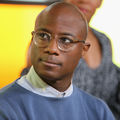 Barry Jenkins. Black man in blue sweater and light blue dress shirt and brown glasses in front of yellow background and black woman in blue blouse