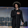 "Colin Kaepernick. Black man with black afro and beard stands in black suit with black t-shirt and necklace while holding glass award behind black microphone and stand and in front of blue and brown background and grey letters that read ""Sports Illustrated"
