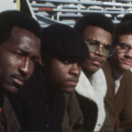 Five Black college students in black and white and brown clothing in front of grey bleachers