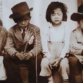 Sepia photograph of two Filipina girls and two Filipino boys in white and brown clothing and black and brown hats in front of white wall
