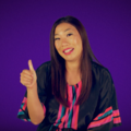 Kristina Wong. Asian woman in purple and pink shirt holding right thumb up in front of purple screen