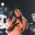 Noname. Black woman in light orange jumpsuit holds microphone in front of Black singer in with blonde dredlocs and black outfit and black background with white lights