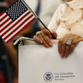 A person holds an American flag as they participate in a ceremony to become an American citizen during a U.S. Citizenship & Immigration Services naturalization ceremony at the Miami Field Office on August 17, 2018 in Miami, Florida.
