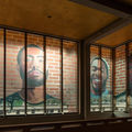 Portraits of Black men on red brick background in brown building