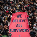 """Dozens of people hold and rally around a massive red sheet with """"We believe all survivors"""" printed on it in navy blue."""