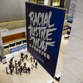 """A convention hall with a large navy blue banner that says """"Racial Justice Now & Forever"""""""