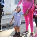 Small children wearing shorts stand with their mother outside a temporary migrant shelter near the U.S.-Mexico border  in Tijuana, Mexico on November 20, 2018.