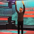 "Hasan Minhaj. South Asian man with black hair and beard holds up hands while wearing black and grey plaid shirt and black pants in front of screen with purple and sea green background and red-orange lines and text spelling ""PATRIOT ACT WITH HASAN MINHAJ"""