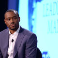 Marc Lamont Hill. Black man in blue suit jacket and white shirt with white screen behind him