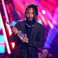 Miguel. Black Latinx man with black dredlocs in black suit and shirt holding silver award statue behind black microphone and stand in front of pink and blue lights
