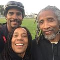 A Black man with long locs poses with his mother and father, who also have locs