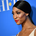 Mj Rodriguez. Black Latinx transgender woman with black hair and red lipstick in beige clothing in front of blue wall with white text