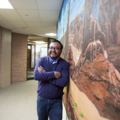 Moroni Benally. Indigenous man in purple sweater and blue jeans and bowtie smiles and leans against portrait of brown and red rocks in front of blue sky in brown hallway