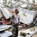 Man stands in front of collapsed building