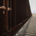 People standing in Mexico reach through and hug the wall at the conclusion of the Hugs Not Walls event on the U.S.-Mexico border in Sunland Park, New Mexico on October 13, 2018.
