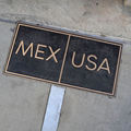 "Black and gold marker on ground reads ""Mex"" and ""USA."""