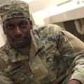 "Emantic Bradford Jr. Black man in green and brown army fatigues and hat with black text reading ""U.S. ARMY"" poses in front of white sink and white and green tiles"