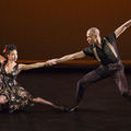 Belén Pereyra-Alem and Yannick Lebrun. Black woman and man in black and brown performance outfits link arms in front of brown wall and floor