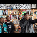 The GZA, Raekwon and the Wu-Tang Clan. Black men in multicolored clothing stand or sit in front of brown bookshelf and multicolored books and artwork