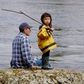 Indigenous man in blue and white shirt sits next to standing Indigenous child in yellow jacket and black pants holding brown stick on brown rocks in front of grey water