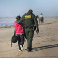 A U.S. Border Patrol agent takes an immigrant into custody after she passed through a breach in the U.S.-Mexico border fence on the beach in Tijuana, Mexico on December 2, 2018.