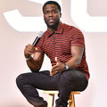 Kevin Hart. Black man in black and red striped shirt and black jeans sits on brown stool and speaks into black microphone in front of light pink wall with white text