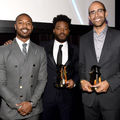 B. Jordan, Ryan Coogler and Nate Moore. Three Black men in gray and black suits pose while holding gold award statues in front of black wall and screen and grey metal rail