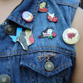 "Multicolored pins, including gold one spelling ""Selena"" and yellow one with text spelling ""COMO LA FLOR"" on denim vest worn by person in black tank top in front of crowd"