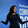 """Sheryl Sandberg. White woman in black dress shrugs shoulders in front of blue screen with white text that spells """"facebook COMMUNITY BOOST"""""""