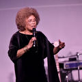 Angela Davis. Black woman with brown afro in black outfit speaks into black microphone in front of drumset and purple screen.